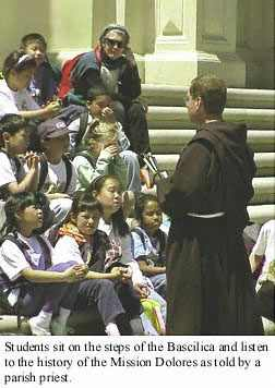 Priest on Bascilica steps explains history of the Mission Dolores to school kids.