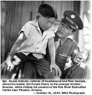 Sgt. Kazuo Komoto shows hist Purple Heart to his brother, Susumu Komoto at the Gila River Relocation Center